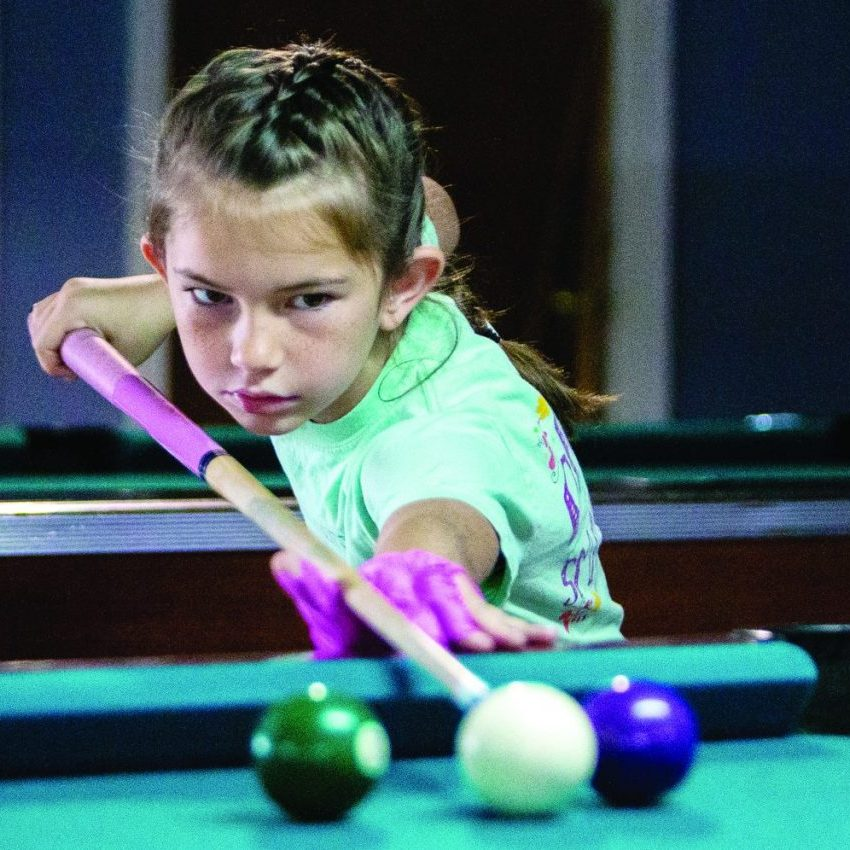 Karleigh Dueitt is shown lining up a shot during a game of pool at GC Pawn and Billiards Monday afternoon. New owners T.J. Dueitt and Jenah Holland are hoping the establishment will provide entertainment options for youth and adults. Photo by Brad Crowe - Herald Staff
