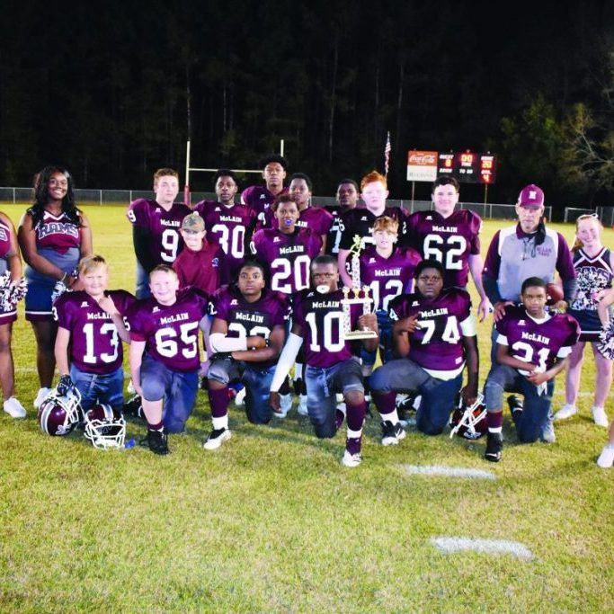 Members of the McLain Rams football team, their cheerleaders and MAC Coach Robert Roper are shown with the Little 6 Conference Championship trophy they had just earned with an exciting 20-8 win over visiting Richton on Monday. The team finished an undefeated season with just four players above the minimum 11 required to be on the field. Team members are Tylan Blackston, Landon Green, Logan Pierce, Dontrey Silas, Ya'Barrai Bolton, Romeco Anderson, Tyland Watts, Samuel Moody, Levi Erkhart, Seth Fairley, Graham Breland, Javon Watts, Brandon Wash, Lucious Moye and Nick Hobby. Cheerleaders are Sadie Breland, Elizabeth Clark, Jalexus Fairley and Akeelah Hartfield. Photo by Russell Turner - Herald Editor
